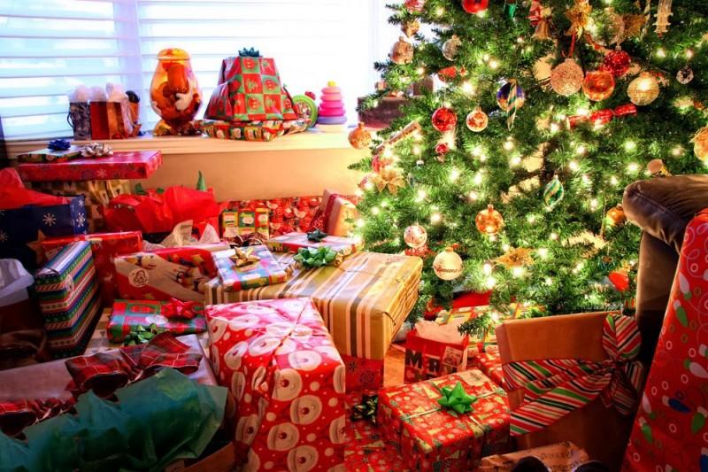 ¡Es Navidad y hay un montón de regalos en el salón alrededor del arbol!