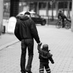 Father having a walk in the city with his little boy