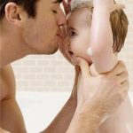 Funny baby having a bath with his father