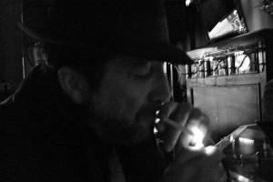 Con sombrero y encendiendo el cigarrillo