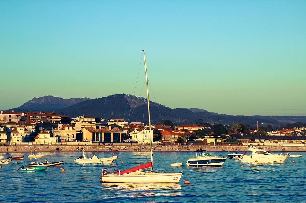 Barcos en el mar puerto de Panxón con playa América al fondp autor Manuel Ramallo