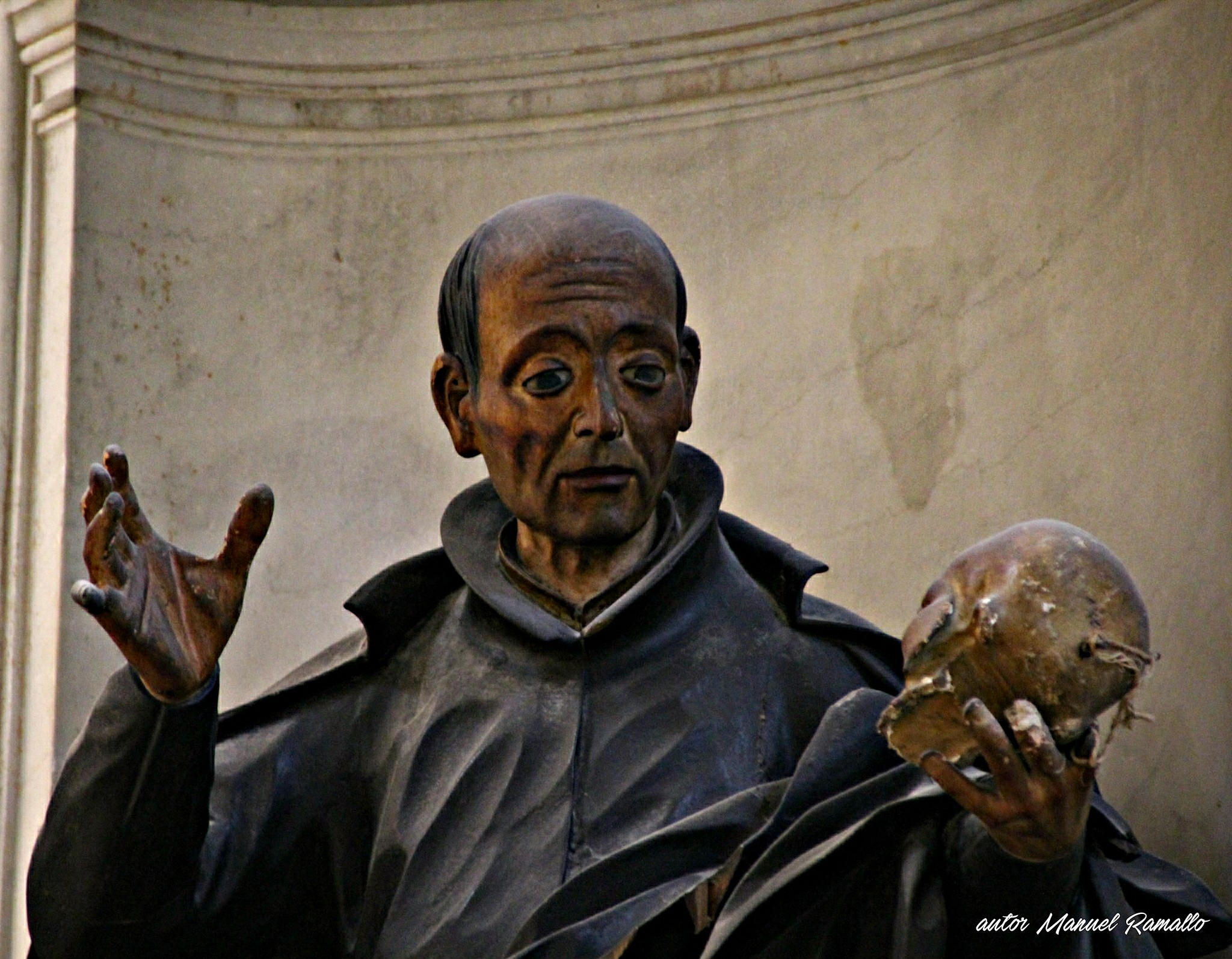 Escultura imagen religiosa monje santo observando una calavera cráneo en la mano izquierda