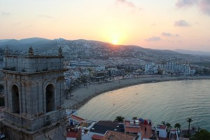 Playa de Peñíscola con el sol rojo en el horizonte desde el castillo fortaleza del Papa Luna
