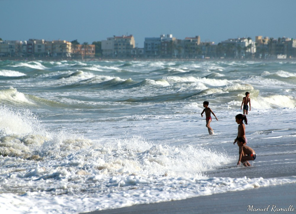 Niños en la playa de Peñíscola jugando con las olas