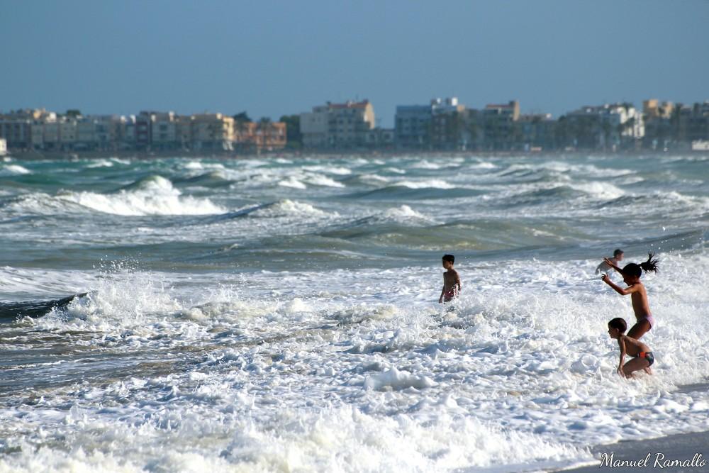 Playa de Peñíscola Niños en el agua olas espuma